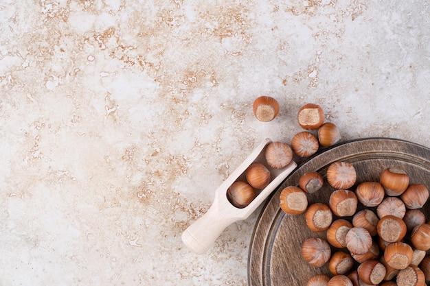 Uma tábua de madeira cheia de nozes de macadâmia saudáveis