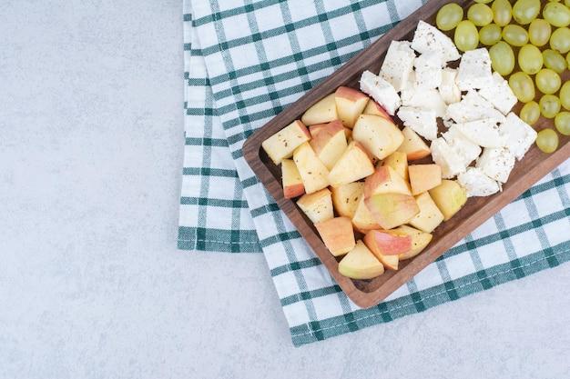 Uma tábua de madeira cheia de queijo branco e frutas fatiadas.