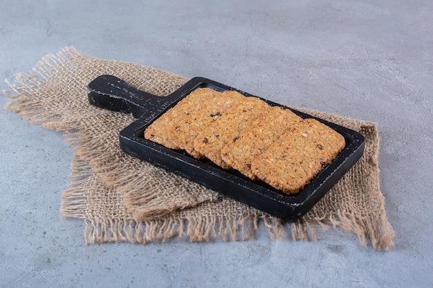 Uma tábua de madeira com barras de granola saudáveis em uma superfície de pedra