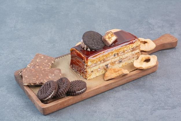 Uma tábua de madeira com biscoitos e um pedaço de bolo