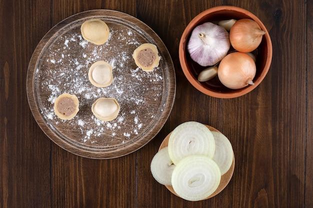 Uma tábua de madeira com bolinhos pelmeni caseiros com uma tigela de barro com cebolas.