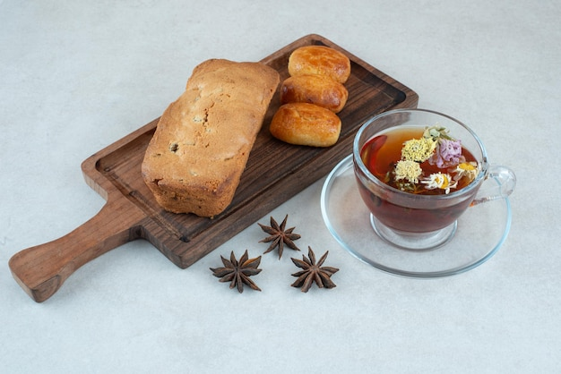 Uma tábua de madeira com bolo e chá de ervas.