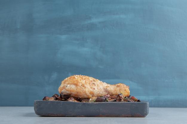 Uma tábua de madeira com carne de coxa de frango frito e berinjela.