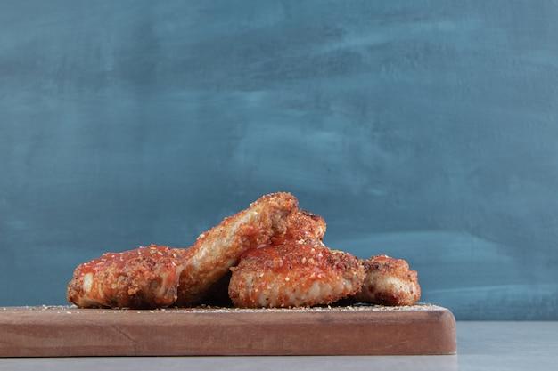 Uma tábua de madeira com carne de frango frito com tempero.