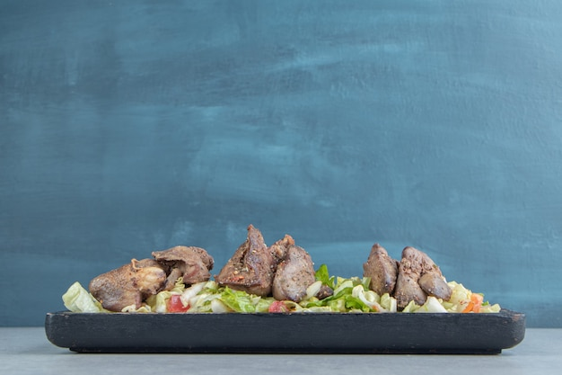 Uma tábua de madeira com carne de frango frito.