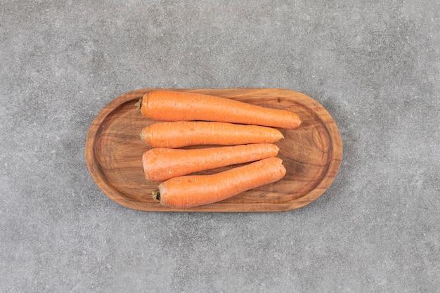 Uma tábua de madeira com cenouras doces frescas colocadas sobre uma superfície de pedra.