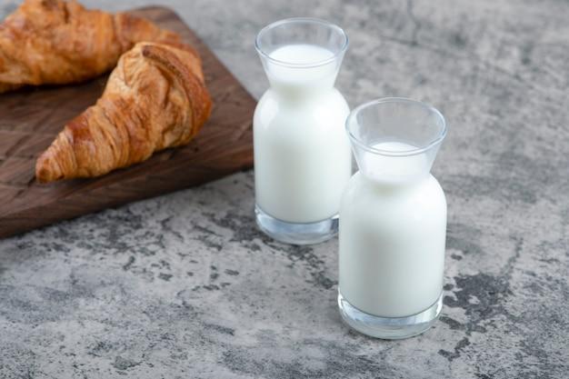 Uma tábua de madeira com croissants frescos e jarras de vidro branco com leite.