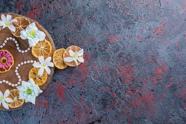 Uma tábua de madeira com fatias de limão seco e flores coloridas com pérolas.