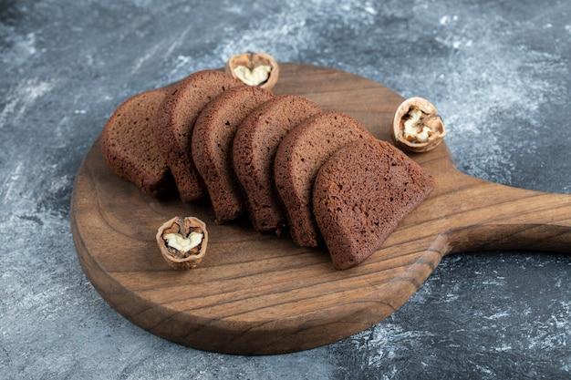 Uma tábua de madeira com fatias de pão e nozes.