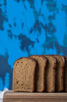 Uma tábua de madeira com fatias de pão integral.
