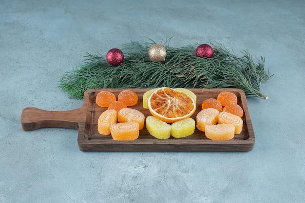 Uma tábua de madeira com geleias de laranja e frutas secas.