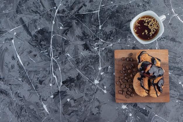 Uma tábua de madeira com minicroissants com chocolate e grãos de café.