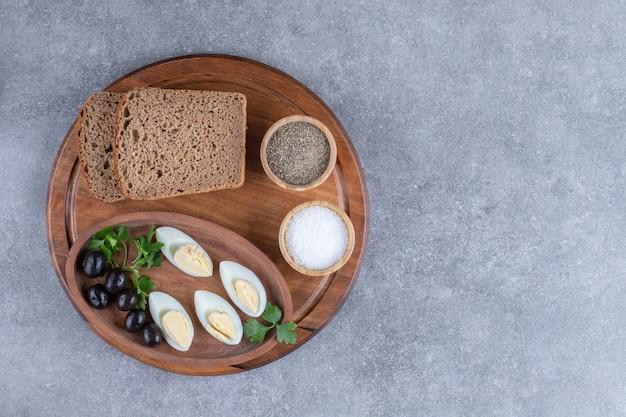 Uma tábua de madeira com ovo cozido e fatias de pão