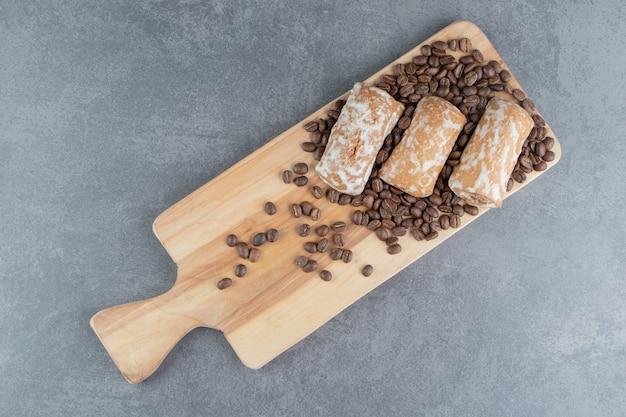 Uma tábua de madeira com pão doce de gengibre e grãos de café