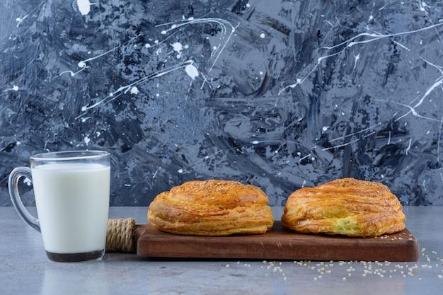 Uma tábua de madeira com pastelaria nacional do azerbaijão com um copo de leite fresco