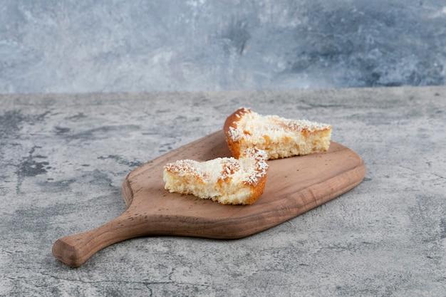 Uma tábua de madeira com pedaços de um delicioso bolo sobre uma mesa de mármore.