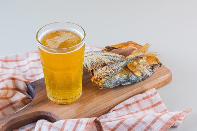 Uma tábua de madeira com peixes secos com uma caneca de cerveja em um saco
