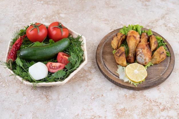 Uma tábua de madeira com pernas de frango frito, carne e vegetais