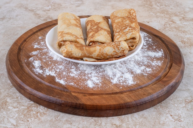 Uma tábua de madeira com saborosos crepes caseiros