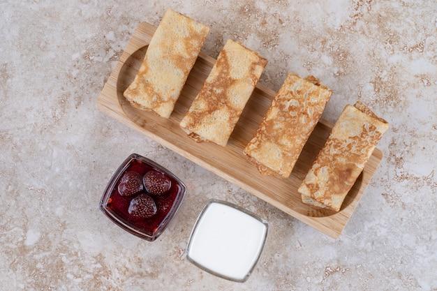 Uma tábua de madeira com saborosos crepes e geléia de morango