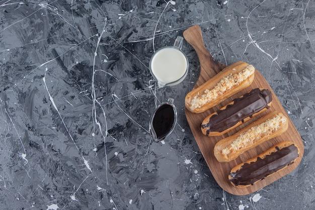 Uma tábua de madeira com saborosos éclairs com uma jarra de leite fresco.