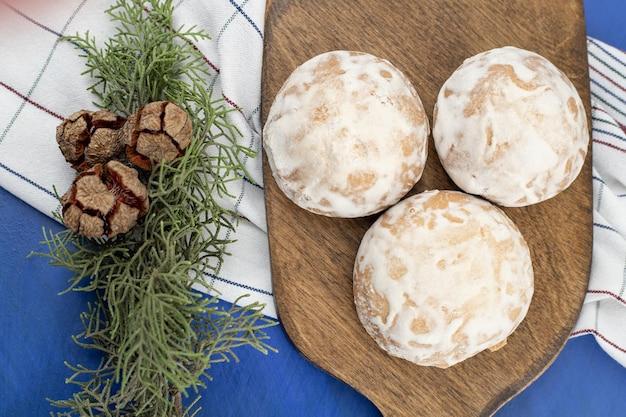 Uma tábua de madeira com três biscoitos de gengibre e pinhas