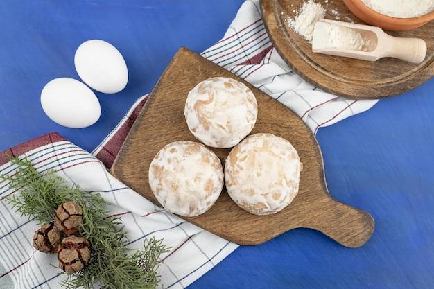 Uma tábua de madeira com três biscoitos de gengibre e pinhas.