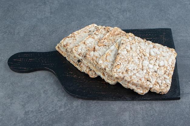 Uma tábua de madeira com waffles de arroz crocantes.