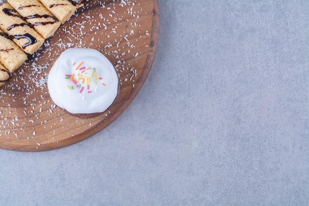 Uma tábua de madeira de palitos doces com bolinho cremoso com granulado colorido.