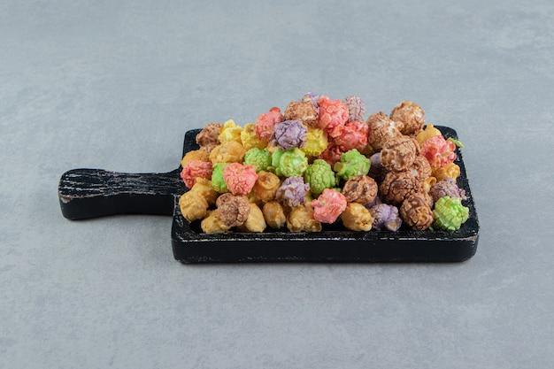 Uma tábua de madeira escura cheia de pipocas doces multicoloridas.