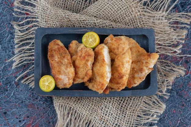 Uma tábua de madeira escura com carne de frango assada com rodelas de limão.