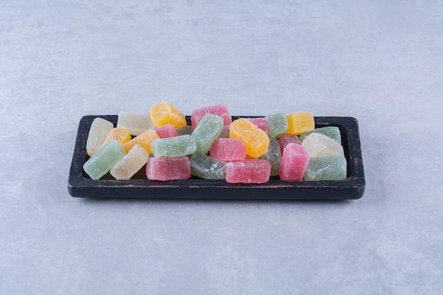 Uma tábua de madeira preta cheia de doces coloridos de frutas