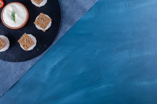 Uma tábua de madeira preta com pequenos sanduíches com uma tigela de maionese de barro.