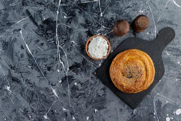 Uma tábua de madeira preta de gohal azerbaijani e uma tigela de barro com farinha