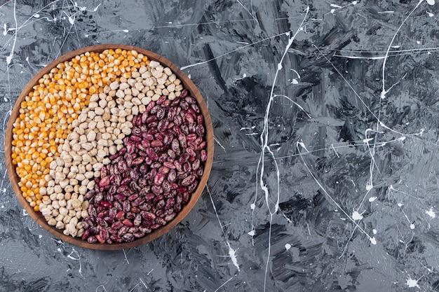 Uma tábua de vários cereais, grãos, sementes, sêmolas, leguminosas e feijão.
