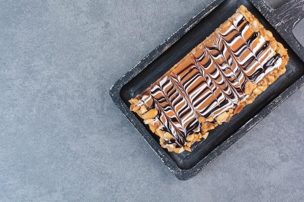 Uma tábua escura de bolo doce na mesa cinza.