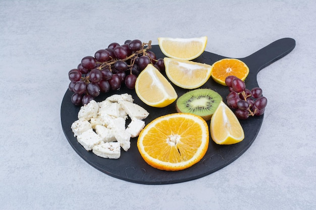 Uma tábua escura de frutas doces frescas e queijo branco fatiado.