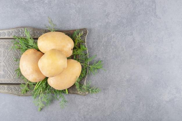 Uma tábua preta de batatas cruas com endro fresco