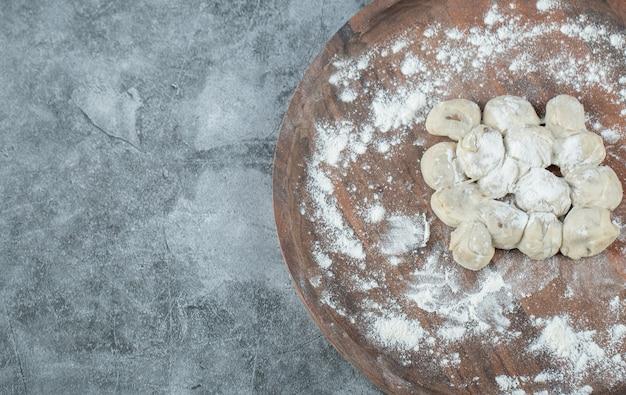 Uma tábua redonda de madeira com bolinhos de massa crus e farinha.