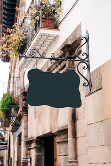 Uma tabuleta vazia de uma forma bizarra está pendurada em um lindo pino forjado na fachada de um prédio antigo