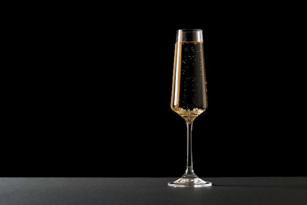 Uma taça cheia de champanhe em uma superfície preta