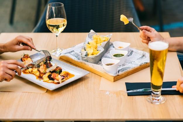 Uma taça de cerveja e vinho em uma mesa com pratos que duas meninas almoçam juntas em um restaurante no terraço