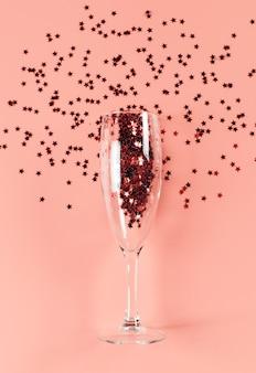 Uma taça de champanhe cheia de confetes de estrelas em um fundo rosa pastel. cartão em branco.