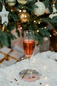 Uma taça de champanhe rosa com glitter em um suporte de mármore, manta de malha, luzes de natal. férias, festa, ano novo. árvore de natal.