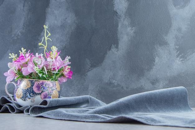 Uma taça de flores em um pedaço de tecido, na mesa branca.