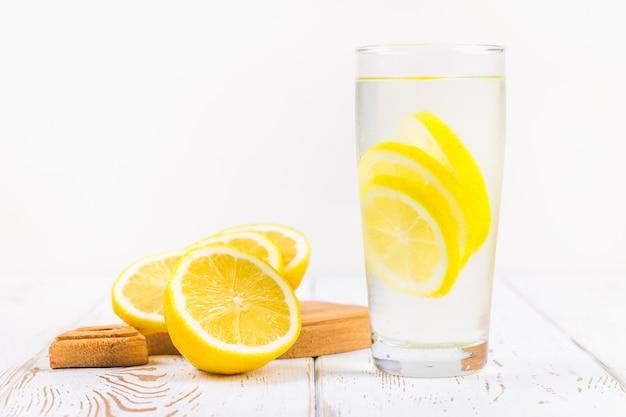 Uma taça de vidro e um jarro de limonada fria em um fundo de madeira branco cercado por limões.