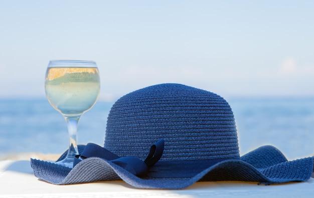 Uma taça de vinho branco e um chapéu azul atrás do relaxamento do conceito de férias de verão do mar da lagoa