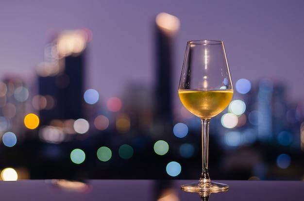Uma taça de vinho branco na mesa do bar da cobertura com luzes coloridas do bokeh da cidade