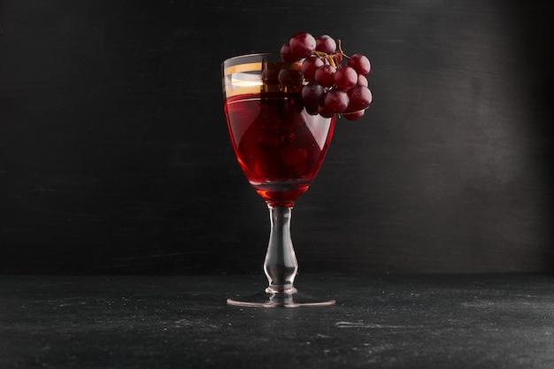 Uma taça de vinho com um cacho de uvas na superfície preta.