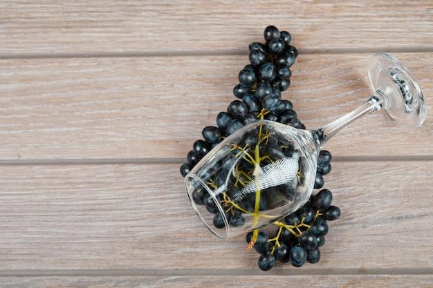 Uma taça de vinho e um cacho de uvas vermelhas.